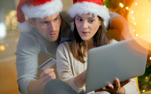 Couple buying Christmas gifts online with laptop